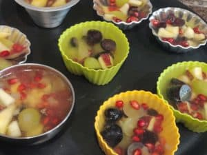 pour warm Agar solution over fruits
