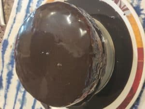 Pouring the melted ganache on the cake
